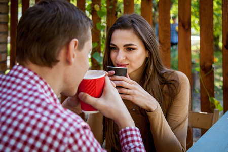 A guy and a girl drink coffee in the park on the terrace in a cafe