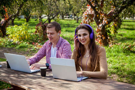 A guy and a girl sit at a wooden table in the park and work on laptops with headphones. Freelance work outdoors. Working outside the office due to the Covid 19 pandemic