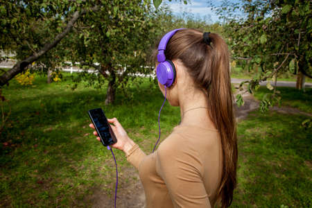 The girl listens to her favorite music from the phone in purple headphones in the park..Girls in the park listening to music