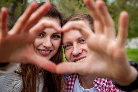 A loving couple in a good mood in the park, shows a heart from the fingers. Young couple in the park