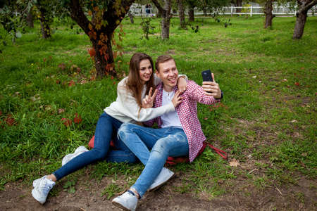 A young couple spends time together in the park, sitting on the grass, making selfies on the phone. The guy with a girl with gadgets in the park 版權商用圖片