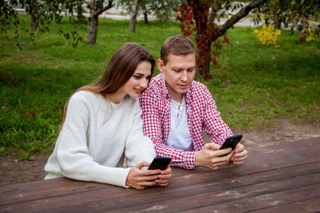 A young couple spends time together in the park, sitting at a wooden table and looking into their phones. Guy with a girl with gadgets in the park