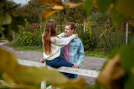 Couple in love in a good mood hugging in the autumn park. Young couple in the park