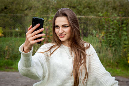 A beautiful young girl with long hair in a white sweater makes a selfie on the phone.
