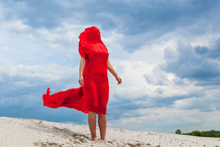 A girl in a red cloth on the sand poses for a photographer against the backdrop of a cloudy sky. Red fabric in the wind hugs the girl's figure. 版權商用圖片