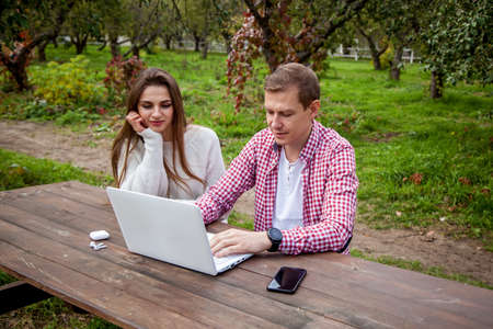 Smiling young couple spend time together in the park, study and work while sitting at a wooden table with a laptop. Guy with a girl with gadgets in the park