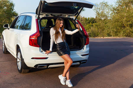 Beautiful sexy girl with long hair in a short leather black skirt and a white sweater posing near the open trunk of a white  . Girl posing near the car