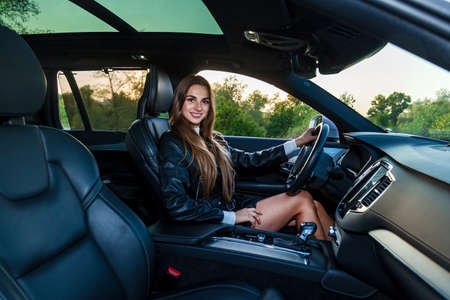 Young brunette girl with long hair in a leather black jacket and a skirt with beautiful legs driving an expensive car. Young girl driving a car 版權商用圖片