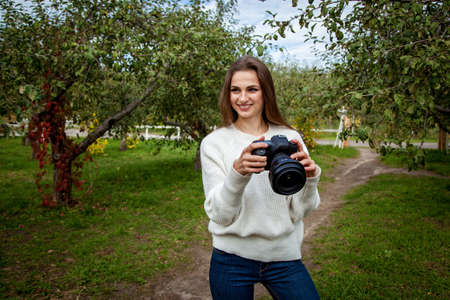 Girl photographer in a white sweater and jeans takes a picture on a professional camera in the park 版權商用圖片