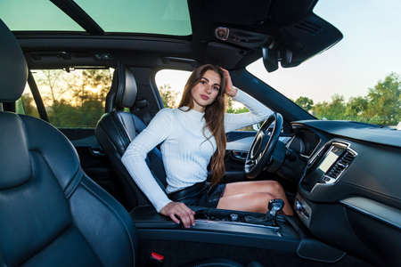 A young brunette girl with long hair in a white sweater and leather black skirt with beautiful legs driving an expensive car 版權商用圖片