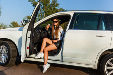 Beautiful sexy girl with long hair in a short leather black skirt and a white sweater poses near the open door of a white jeep. Girl posing near the car