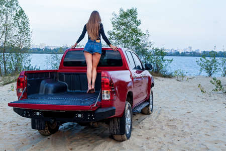 Beautiful sexy girl with long hair in short denim shorts and a black bodysuit posing in the open body of a red pickup truck. Girl posing near the car