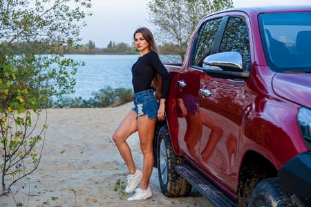 Beautiful sexy girl with long hair in short denim shorts and a black bodysuit posing near a red pickup truck. Girl posing near the car