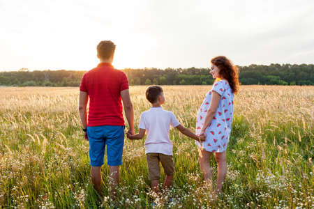 A husband, his wife, and a young son are posing on the wheat field at sunset.