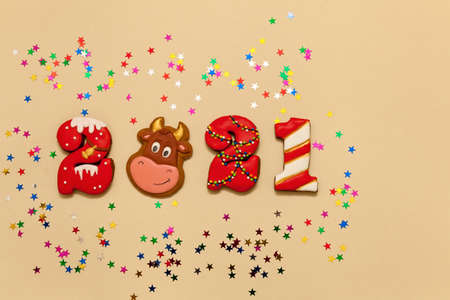 Numbers 2021 from gingerbread cookies in multicolored glaze on a beige background. The symbol of the year bull and multicolored stars. New year 2021, Christmas holiday