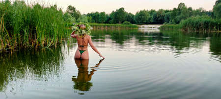 A girl in a swimsuit and with a bouquet of flowers on her head, stands in the water on the holiday of Ivan Kupala