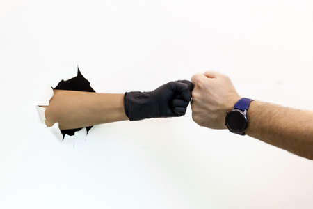 Female and male hands, one in a protective glove and the other without a glove, two people handshake on a white background