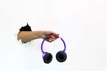 A female hand with a red manicure through torn white paper holds a wireless purple headphone. Hand through torn white paper Foto de archivo