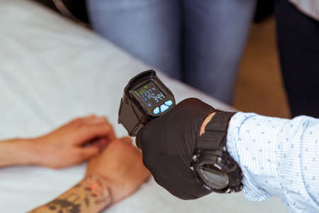 A male hand in a black glove measures the temperature on the patient's arm.