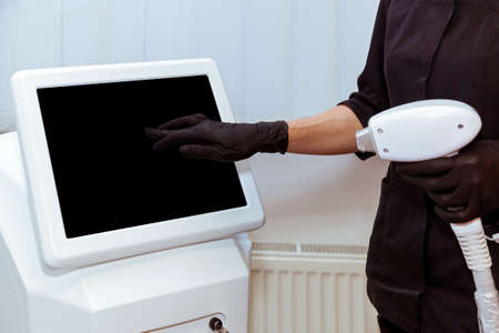 The hand of a beautician in a glove presses the monitor in a modern laser machine. Hand presses the monitor on the apparatus Foto de archivo