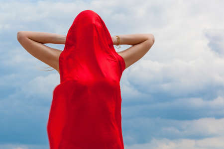 A girl in a red cloth on the sand poses for a photographer against the backdrop of a cloudy sky. Red fabric in the wind hugs the girl's figure. Foto de archivo