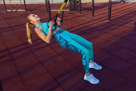The girl does exercises with fitness belts  on the playground. Fitness in the street. Attractive girl doing exercises on the sports field. Sportswear for fitness. Fitness exercises with loops. Healthy lifestyle. Foto de archivo