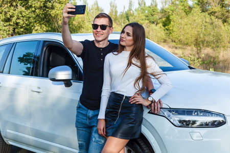 Young couple takes a selfie near the white car.A guy with a girl take a selfie near the car