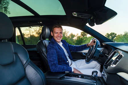 A guy in a plaid jacket and white trousers smiling sits behind the wheel of an expensive car Foto de archivo