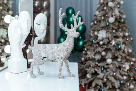 A toy silver deer stands on the table against the background of a Christmas tree, balloons and masks Foto de archivo