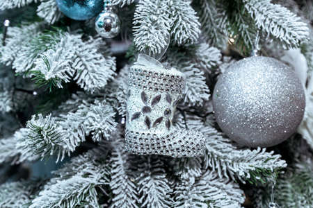 Christmas tree decorated with silver Christmas toys close-up. Silver Christmas toys on the Christmas tree