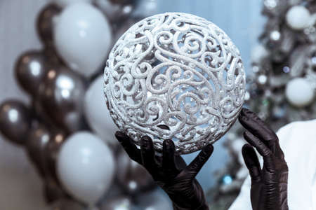 Female hands in black medical gloves hold a silver balloon against the background of a christmas tree and balloons