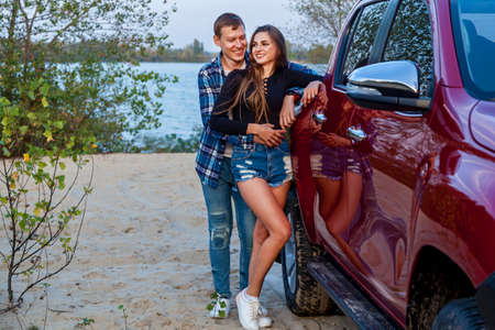 Happy young couple in love smiling and hugging next to red car on the beach near the lake. Young couple hugs near the car.