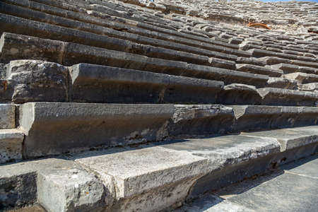 Stone steps of an old amphitheater from ancient times in the region of Antalya, Side, Turkey.