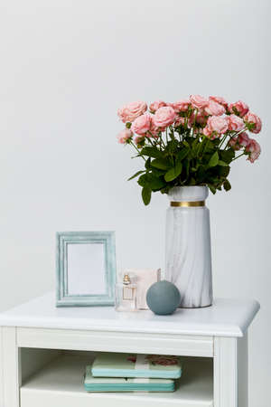 White bedside table near the bed against a white wall. On the bedside table, there are items of a vase with roses, a round candle, a photo frame, and eau de toilette Foto de archivo