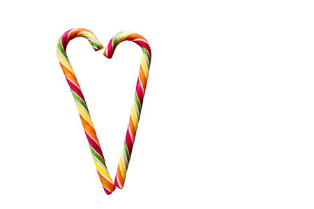 Multicolored striped heart-shaped lollipops on a white background. Christmas, New Year, Valentine's Day, winter holiday atmosphere for lovers Foto de archivo