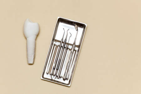 Dental implant, dental tools on a beige background. Dental implant model of artificial tooth. Concept of dentistry and medical instruments. Photo with place for your text and design.