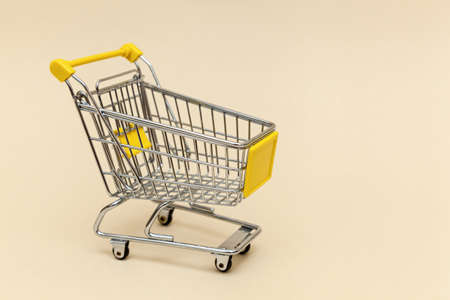 Metal shopping cart on a beige background. Concept objects for supermarket. Photo with place for your text and design.