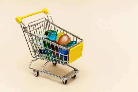 Metal shopping cart with colored stones on a beige background. Concept objects for supermarket. Photo with place for your text and design. Foto de archivo