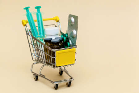 Metal shopping cart with tablets, injections and syringes on a beige background. Medicine concept. Photo with place for your text and design.