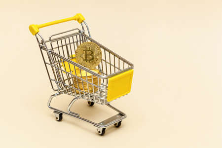 Metal shopping cart with bitcoints on a beige background. Money concept.Photo with place for your text and design.