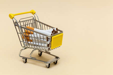 Metal shopping cart with cigarettes on a beige background. Concept objects for supermarket. Photo with place for your text and design.