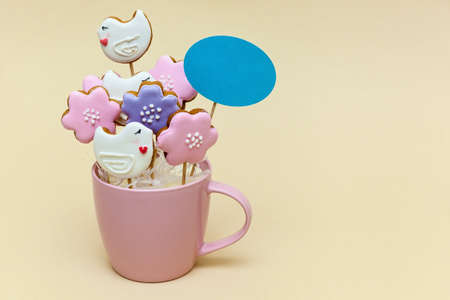 Pink mug with cookies on a skewers on a beige background. Food concept. Photo with place for your text and design.