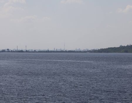 dniper: Television tower and distant profiles of buildings of the big city in a blue haze. In the foreground is a wide expanse of water. The city of Kiev in the background and the city Vyshgorod nearterm on the right. View from the Kiev reservoir.
