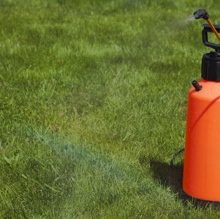 farme: Device of spraying pesticide at the sunshine produces a rainbow over green grass.