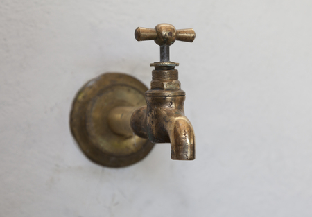 spigot: On the white wall the old brass faucet.