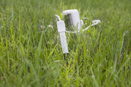 farme: Summer, the white small flowers and green grass. At the sunbeam bright gray plastic plug appliance for measuring, inserting in the ground in the center at sunbeam. In the background is blurred device on blurred grass.