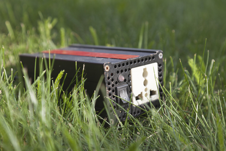 Device of black color with red strip on green grass in a sunbeam. This inverter used for convert electricity from solar panels.