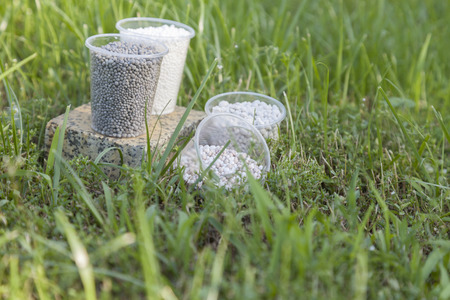 In the bright sunbeams fertilizer in plastic cups on a granite stand surrounded by bright green grass. Stock Photo