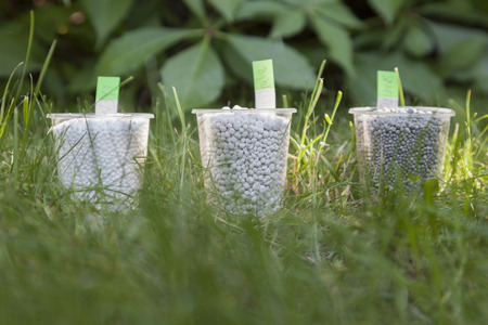 In the bright sunbeams fertilizer in plastic cups surrounded by bright green grass. On the stickers is recorded of fertilizer formula. Stock Photo