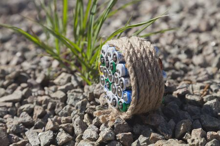 farme: Batteries wrapped a rope on the broken stone and blurred grass at background.